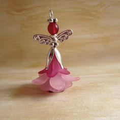 """,, KVĚTINOVÁ ANDĚLKA """" č.6 Květinová andělská holčička je vyrobená z akrylových a skleněných korálků ve tvaru zvonečku a květu. Tělíčko je dotvořeno ozdobných kaplíkem, andělskými křidélky a svatozáří z bižuterních komponentů ve stříbrné barvě. Andělská holčička má očko na zavěšení na mobil, na záložku, na klíče, na kůži, řetízek atd.  ..."""