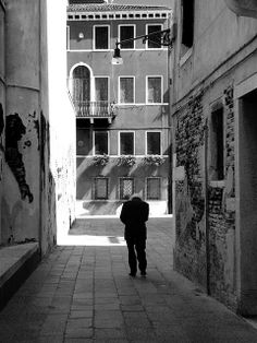 Lonely, old italian man in an alley in Venice on a sunday morning, going to the church