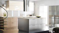 Cocina con puertas en alto brillo y frentes de cajón de acero inoxidable y efecto nogal