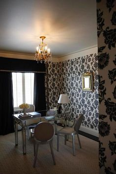 Stunning black and and white floral wallpaper surrounds this elegant, transitional office. A small gold chandelier and gold framed mirror add to the formal look while a metallic desk with silver chairs adds a sharp, contemporary touch.