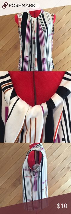Fun blouse This fun dynamic blouse is beautiful on! Looks great under a blazer or over dress pants. Perfect edition to your work wardrobe. White background, black, brown, purple, and orange stripes. Worthington Tops Blouses