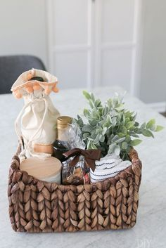 Create this adorable and simple #housewarming gift for new homeowners. Buy a basket and fill it with wine, olive oil, new towels, and all kinds of pretty items. #giftidea #newhomeowner #housewarminggifts