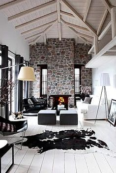 love the high beamed ceilings and stone wall and fireplace