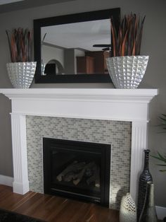 DIY fireplace decorations: I purchased two large vases at Home Sense to flank each side of the fireplace, but they lacked height. To solve my problem, I cut a piece of styrofoam to fit inside the vases. I then cut some decorative leaves to desired size and arranged/stuffed them in the styrofoam. Worked out great!