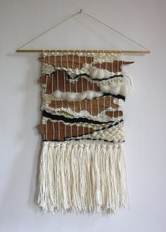 Handwoven wall hanging on a hollow brass rod. Fiber materials are a mix of cotton, natural wool roving, and found tree bark from my Chicago