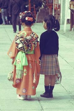 Two little girls, one in kimono and one in a school outfit.
