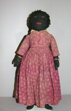 "PRIMITIVE BLACK CLOTH DOLL, 18"". Black sateen head and torso, wide hips, attached limbs and mitten hands. Curly black wool hair with a few t..."