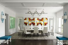 A pair of sconces by Hervé Van der Straeten flank the entrance to the dining room, which features a 1970s Sciolari light fixture above a custom-made dining table and 1950s Dunbar chairs covered in a Rogers & Goffigon linen; the painting is by George Condo, and the large-scale metal piece is by Jim Lambie.