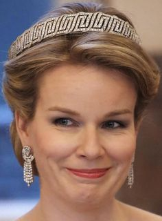 Queen Mathilde of Belgium wearing the bandeau portion of the Nine Provinces tiara. This tiara was a wedding gift from the people of Belgium to Princess Astrid of Sweden, who married the future King Leopold III in 1926. Created by Belgian jeweler Van Bever, the original version of the diadem is a flexible diamond bandeau in a stylized Greek key motif topped with 11 large diamonds on spikes. These large stones, totaling around 100 carats on their own, symbolize the nine provinces of Belgium