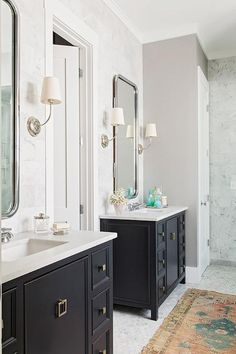 Beautifully designed gray and black bathroom features a door flanked by two black washstand with brass square pulls topped with white quartz countertops fitted with undermount sinks and polished nickel faucets positioned beneath curved metal vanity mirrors illuminated by Vendome Single Sconces mounted on a marble wall.