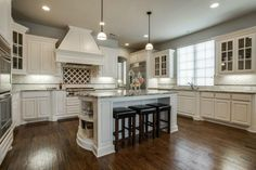 Traditional kitchen with off white cabinets and dark maple floors