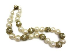 A beautiful vintage faux pearl necklace with brass filigree bead caps, by Miriam Haskell.  There is some wear to the finish on the pearls, and the