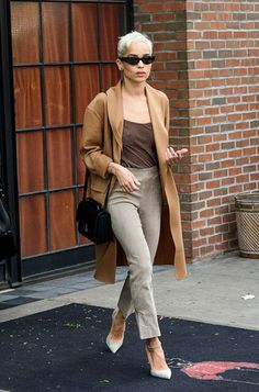 Zoë Kravitz in a pair of grey pencil trousers, Mary Jane heels, and a camel jacket layered over a brown tank