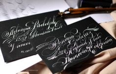 This super flourished calligraphy script is done using a traditional dip nib. It has way more swirls and flourishes and is almost illustrated rather than written. More info here: http://openinkstand.etsy.com