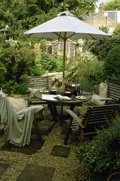 A table and chairs with an umbrella on a backyard patio.  Great idea for over by the orchard and greenhouse