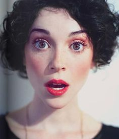 Cute as a button Annie Clark, short curly look, by tied back hair