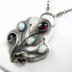 """Grow With the Flow Necklace  Garnet Opal and Sterling by glowfly, $210.00 ::: A hand-cut pendant of sterling silver has grasses and flowers sprouting out of it: at the top, a fully-bloomed flower of red garnet, surrounded by smaller buds of opal, with tiny flecks of green and orange inside them. The pendant measures 2"""" long by 1.5"""" wide, with complementary garnet rondelles along the sterling chain that closes with a lobster clasp."""