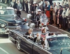 Kennedy smiles at the crowds lining their motorcade route in Dallas on Nov. 22, 1963. Minutes later the president was assassinated as his car passed through Dealey Plaza.