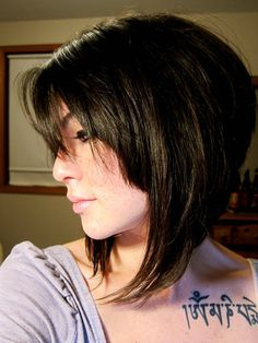 Short, angled hairstyle with bangs. Edgy bob with lots of volume in the back.