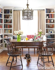 Floor-to-ceiling bookcases give depth to the dining room — office-library.