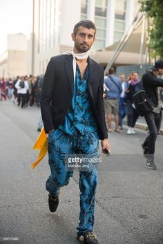 Fashion editor Simone Marchetti wears a skinny white scarf, a black jacket, and blue leaf print Andrea Pomplio top and pants with Gucci Kangaroo fur-lined slippers during the Milan Fashion Week Spring/Summer 16 on September 26, 2015 in Milan, Italy.