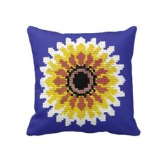 This throw pillow features a bright colorful sunflower with an embroidered look. The sunflower has a dark center and petals in bright red yellow and white radiating radiating from the middle, textured as if they were embroidered on the surface. The background is a dark blue that contrasts well with the sunflower's colors. You can however change the background color using the Customize It button.