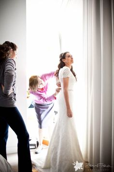 Putting on my wedding dress! Lace wedding dress with sleeves by Paloma Blanca Photography by zevfisher.com