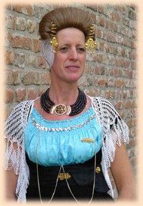 Vrouw in zondagse dracht De Walcherse vrouw draagt een ondermutsje van Zwitserse broderie met daarin het oorijzer met gouden krullen. Aan de krullen hangen gouden klaverbladvormige hangers met een parel, genaamd strikken.. Ze draagt het haar in een brede rolop het voorhoofd: het strêêksel.
