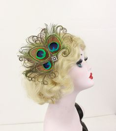 This sparkly fascinator is made from a Swarovski AB crystal covered filigree base that has three delicately curled large peacock...