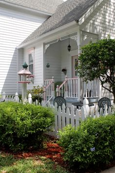 Sweet and simple cottage. So cute. I'd love a little gate like that around a flower garden.
