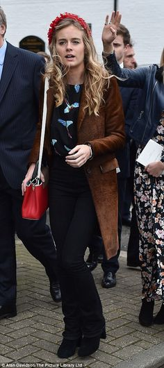 Ms Bonas wore a long brown coat and floral headband, which she matched with a red handbag, for the service in memory of the financier, who died due to a heart condition