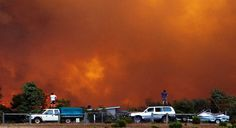 Residents watch a brushfire from the top of their cars in Margaret River, Western Australia, Australia.