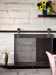 Beautiful sliding fireplace screen. The barn door trend is so fun, but we'd never thought of using it for a fireplace.