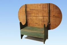 """18th to early 19th century, rare form oval pine hutch table in old green paint, unusually wide seat / bench has lift lid storage compartment, two board wide scrub top, boot jack cutout sides, 72"""" L x 38"""" W x 28"""" H."""