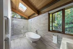 In this modern master bathroom, light colored tile and plenty of windows keep the space bright, while a glass enclosed shower is located at the end of the bathroom, with a freestanding bathtub nearby. Modern Wood House, Modern House Design, Concrete Retaining Walls, Cedar Walls, Modern Master Bathroom, Master Bedroom, House In The Woods, Jacuzzi, House Plans