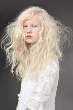 cheveux: ébouriffés makeup : teint pâle/cils blancs expression
