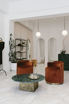 Pink Travertine and Rusty Velvet in a Coolly Minimalist Cape Town Boutique | new store | south africa store | retail store | newest retail stores | interior design | sleek interior design | stores | contemporary stores | modern armchair | orange armchair | marble furniture | marble table | marble interior