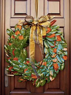 MyHomeIdeas.com - Front-Door Welcome from Coastal Living: A wreath of broad, glossy magnolia leaves adorns the front door at left. Some leaves flip and show off their scuffy brown sides, which adds texture and enhances the wooden door. (Photo: Photo: Deborah Whitlaw Llewellyn; Stylist: Whitney Wise Long; Designer:)