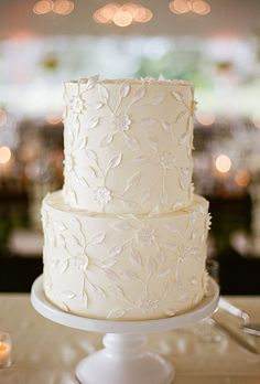 Brides.com: . A two-tier white wedding cake with delicate flower details created by Jim Smeal.