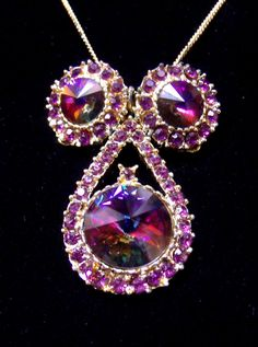 Vintage stunning effervescent, red watermelon rivoli crystal clip on earring and necklace set. There are purple colored ruby rhinestones surrounding