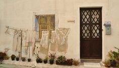 """#Murales in #Sardegna, Murales San Sperate. """"Panni Stesi"""" (1996) Luciano Lixi. Murales dall'illusione architettonica irreale. Un filo di panni, in parte finti in parte veri, stesi ad asciugare al sole, sotto una finestra che sembra reale."""