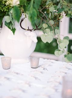 escort card display table with antlered flower vase