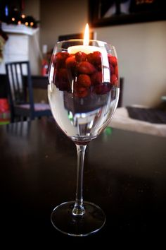 Candle and cranberries floating on water in a wine glass. very simple and cute decoration!