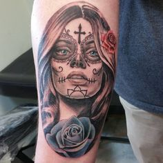 Realistic looking woman's skull on man's forearm with cross, rose and lotus symbols. Beautiful blue eyes exposed