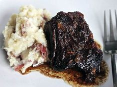 Short ribs braise in a red wine, balsamic vinegar and brown sugar sauce before they're served atop garlic mashed potatoes. Short ribs braise in a red wine, balsamic vinegar and brown sugar sauce before they're served atop garlic mashed potatoes. Boneless Short Ribs, Braised Short Ribs, Braised Beef, Garlic Mashed Potatoes, Mashed Potato Recipes, Mashed Cauliflower, Rib Recipes, Cooking Recipes, Dinner Recipes