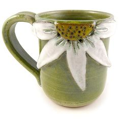 Sculpted Floral Stoneware Mugs. Your new favorite mug! Our large, comfy, wheel-thrown pottery mugs are augmented with your choice of a sculpted daisy or hummingbird design. Crafted with stoneware clay, each mug is high fired for a permanent finish that is microwave and dishwasher safe. Mug holds approximately 14 ounces.