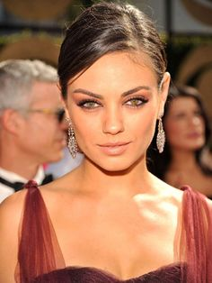 Mila Kunis with seriously sultry eyes (love the perfect winged-out liner!) and a deep side-parted ponytail.
