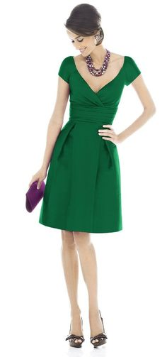 green dress, black pumps, black bib necklace