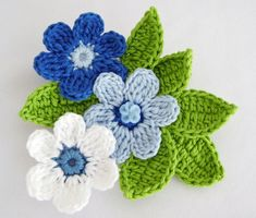 Brooch of Blue & White Crocheted Flowers with Green Leaves from  DaffodilCorneron Etsy. No longer available, but there are a lot of other beauties like this one in her store.