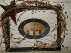 An old frame, stapled chicken wire to the back. Decorated with grape vine, a rusty star, and hung a Wooden plaque in the center.